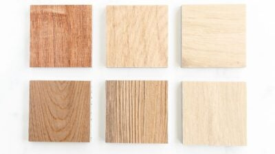 Six small samples of lvp flooring on a white surface.