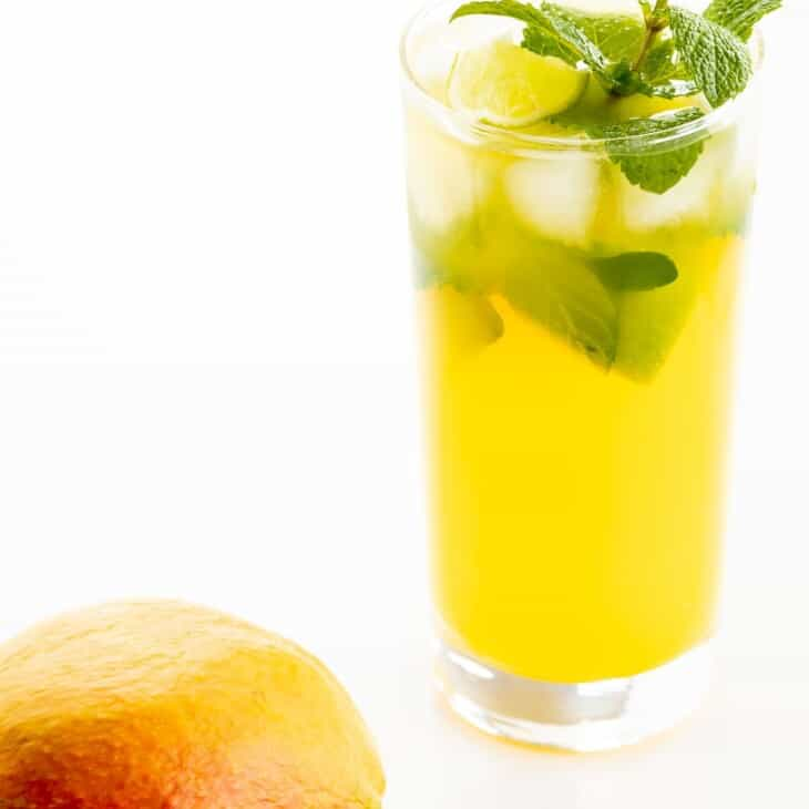 A mango mojito recipe in a clear glass, garnished with a sprig of mint, mango in foreground.