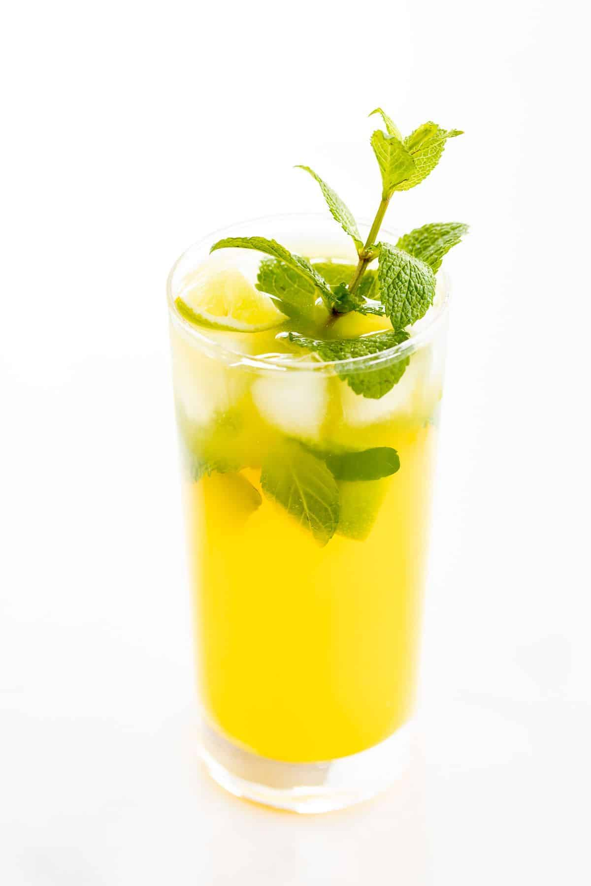 A mango mojito in a clear glass, garnished with a sprig of mint.