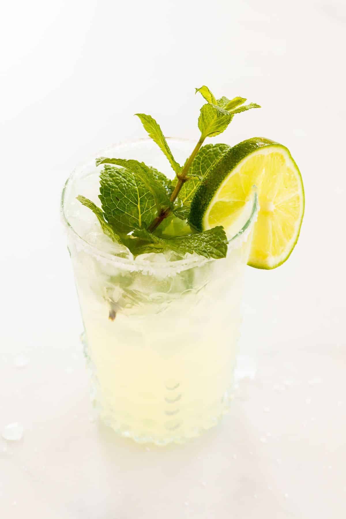 A mint margarita in a clear glass, topped with a sprig of mint and a slice of lime on a white background.