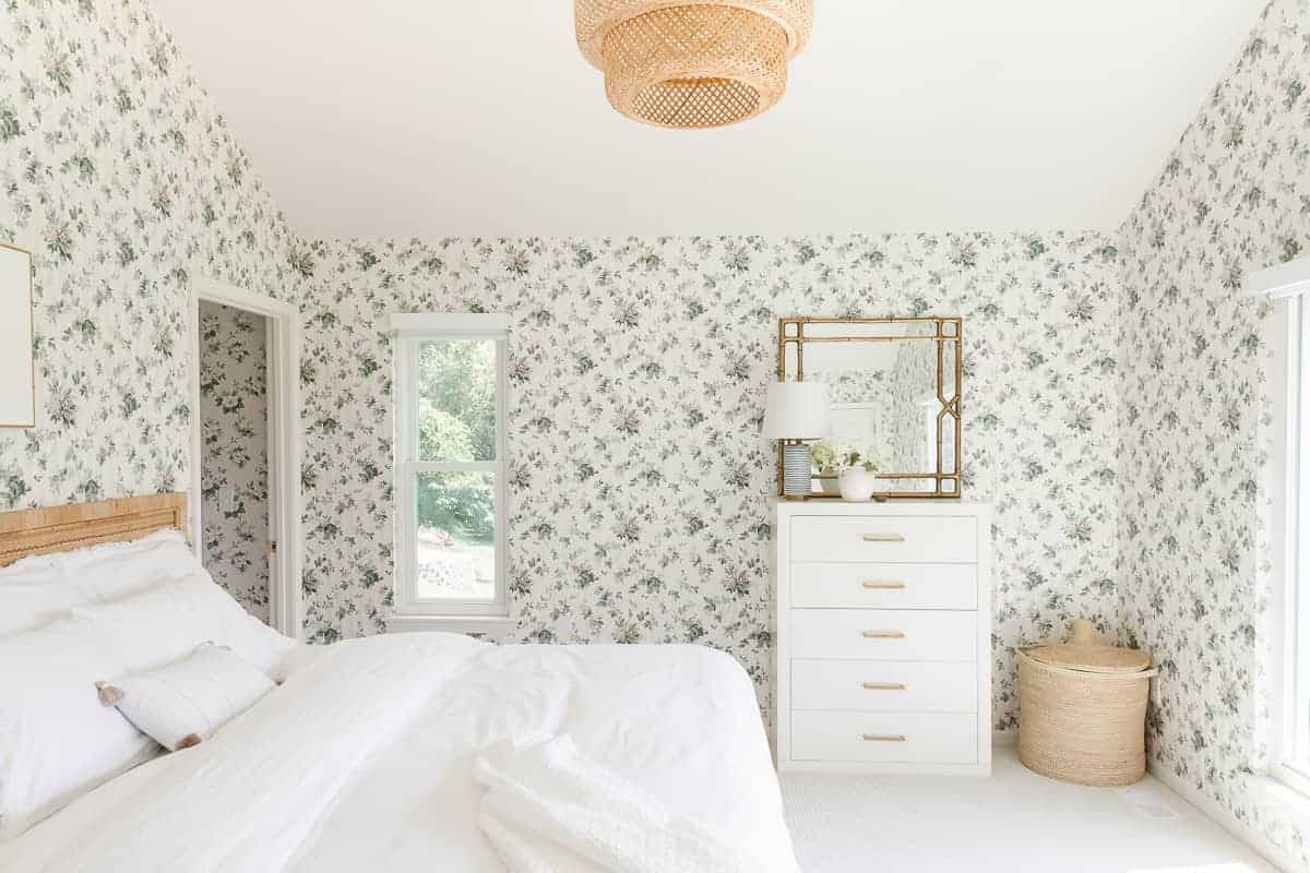 wallpapered bedroom with white dresser and brass pulls