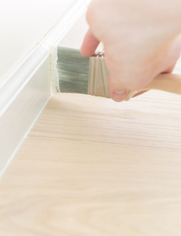A hand painting white trim next to a light wood floor.