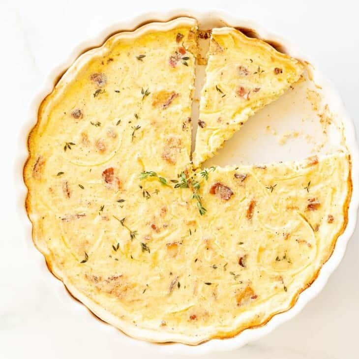 A whole quiche with two slices missing, on a white surface.