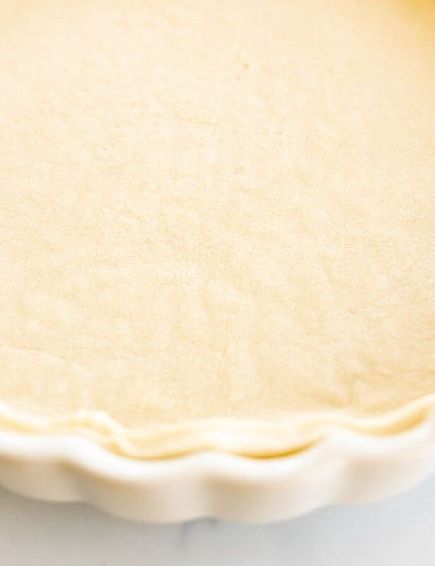 A homemade quiche crust in a fluted pie pan on a white marble surface.