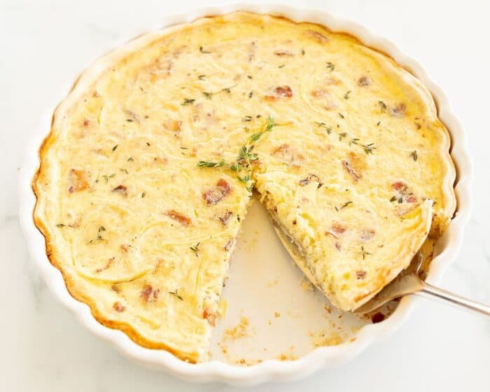 A whole quiche with a slice removed, pie server removing a second in a white pie dish.
