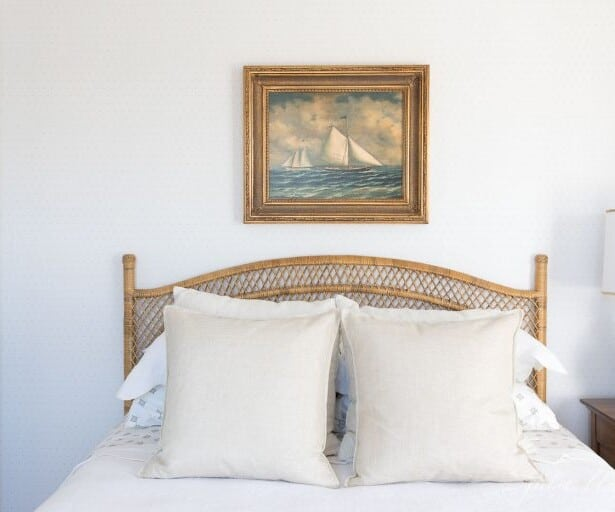 A bedroom with neutral bedding, a rattan bed, and sailboat art above headboard.