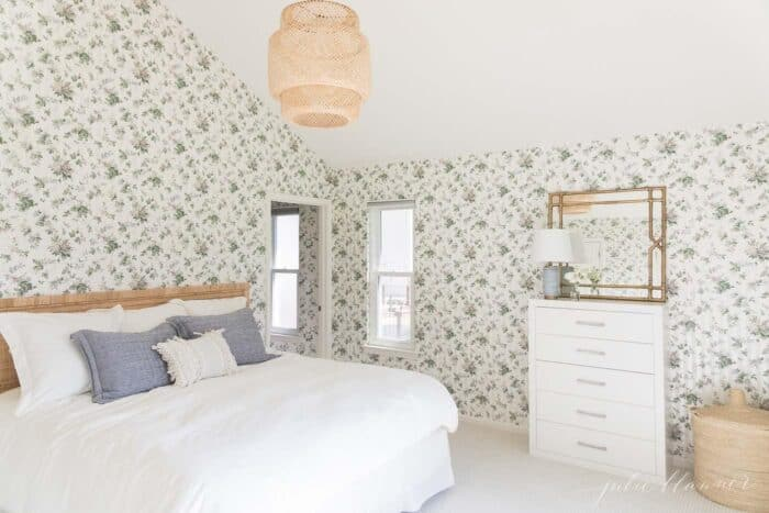 A floral wallpapered bedroom with a rattan bed and white bedding.