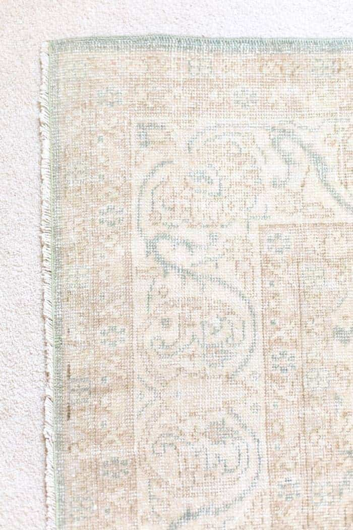 A close up of a vintage Turkish rug on carpet in a bedroom.