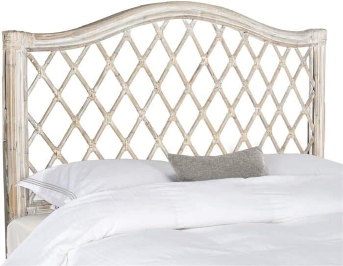 A rattan headboard on a bed with white bedding.