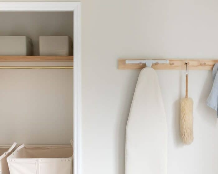 A storage area in a second floor laundry room, with a wooden shelf and peg rail.