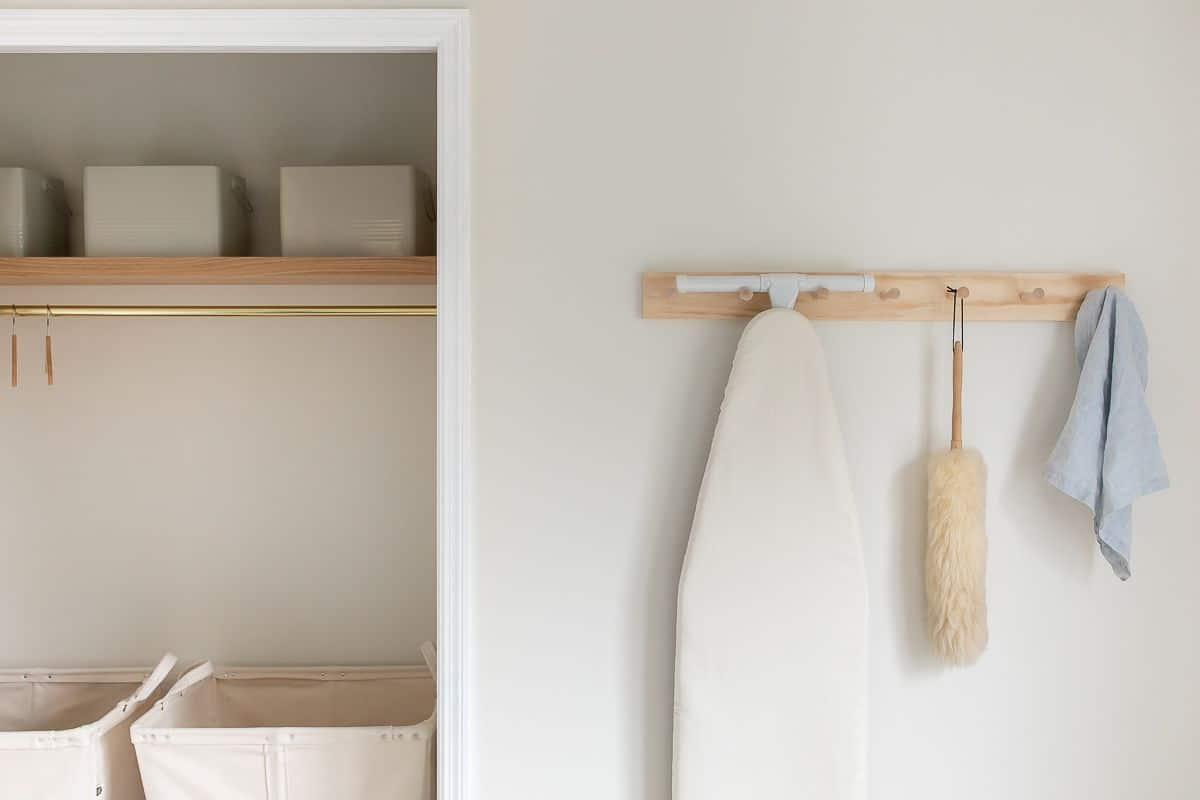 A storage space in a utility room on the second floor, with a wooden shelf and peg rail.