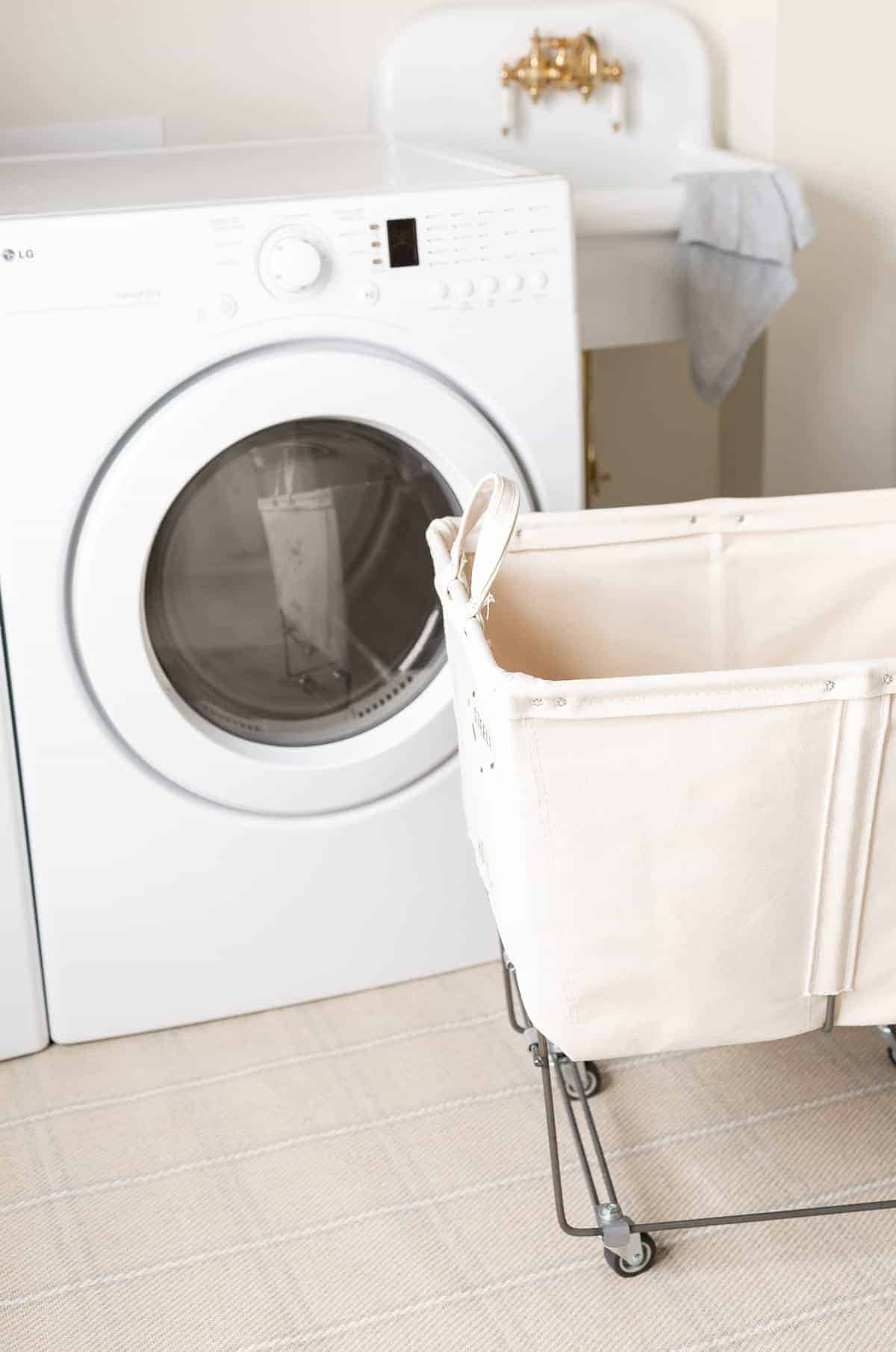 A rolling laundry basket with a washer and dryer in the background.