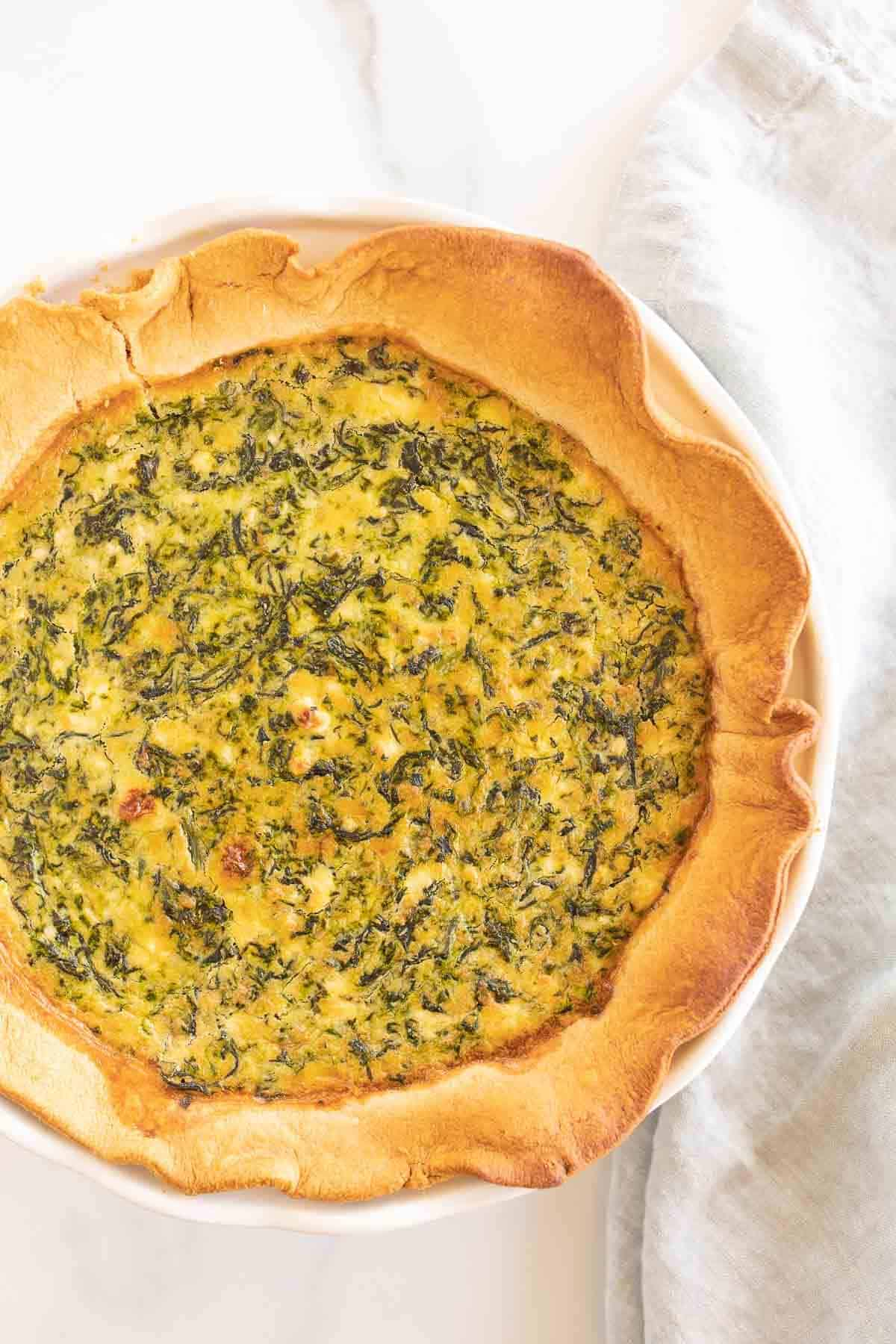 A spinach and feta quiche on a white surface.