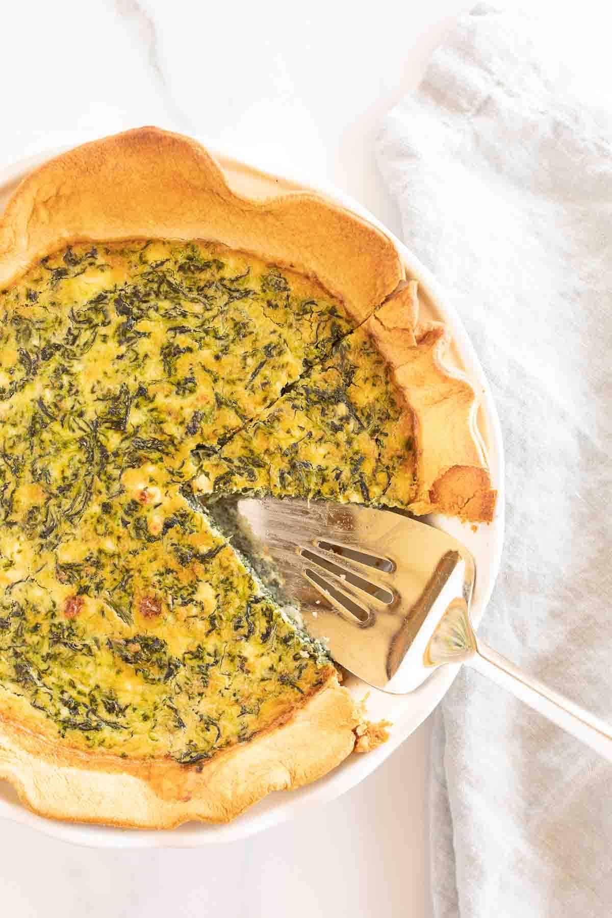 A spinach and feta quiche in a white pie dish, with one slice removed.