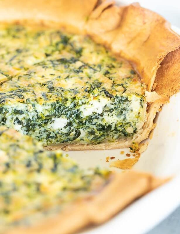 A spinach and feta quiche in a white pie pan, one slice removed.