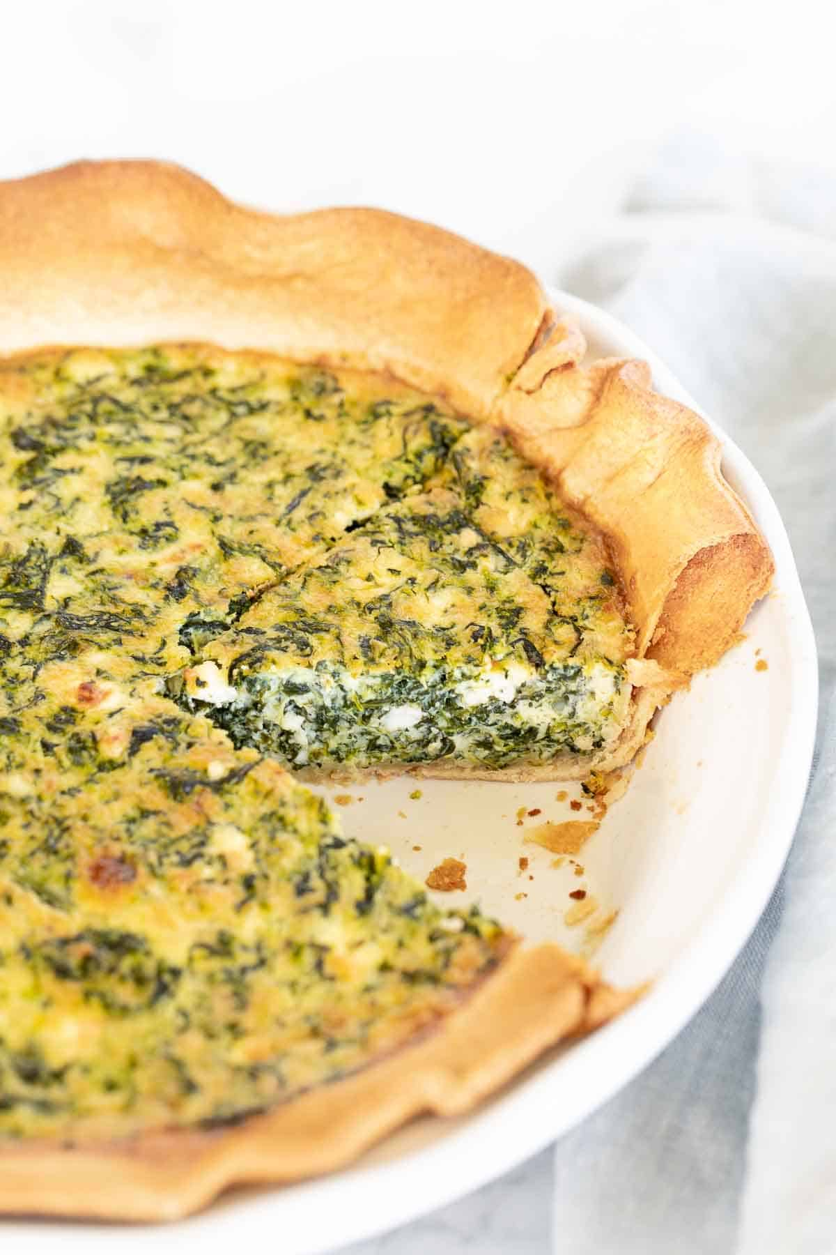 A spinach and feta quiche in a white pie dish, one slice removed.