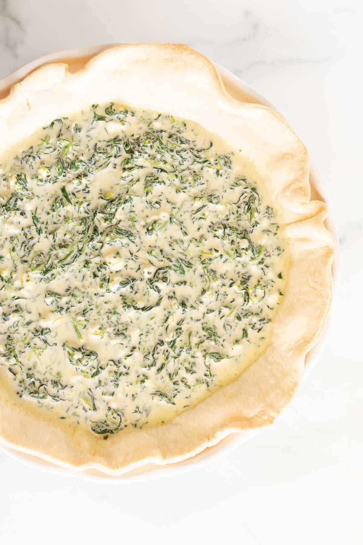 A spinach quiche before going in the oven to be baked.