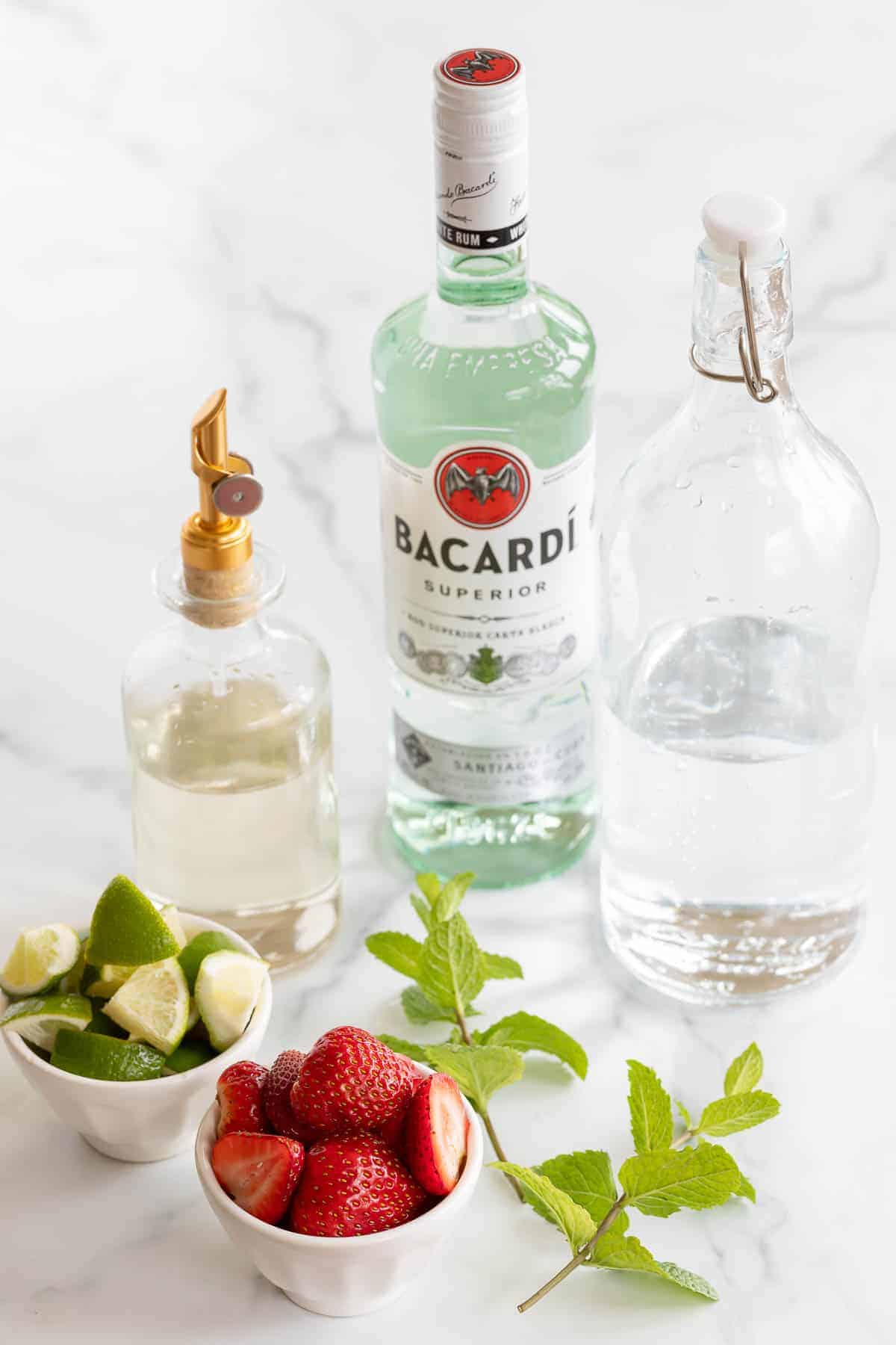rum simple syrup club soda strawberries limes and mint on marble counter