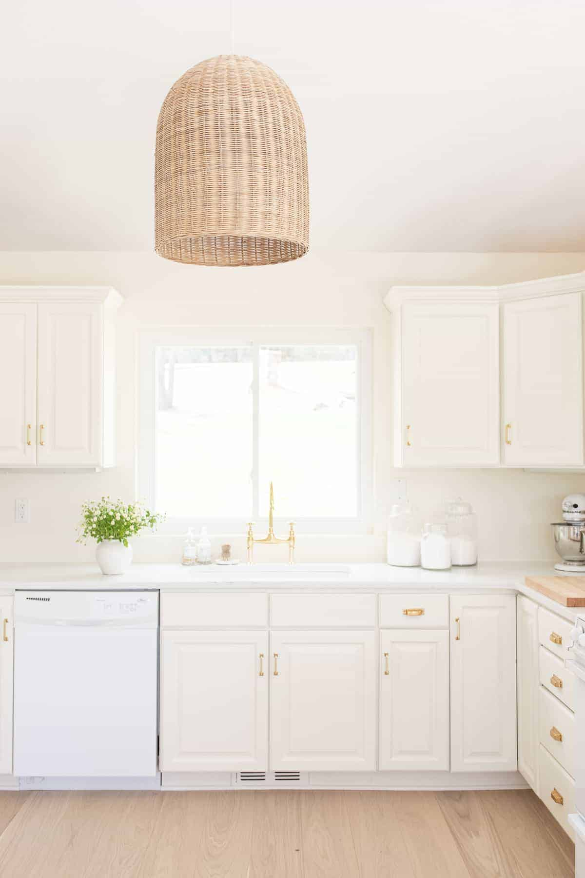 A white kitchen with wide plank white oak floors.