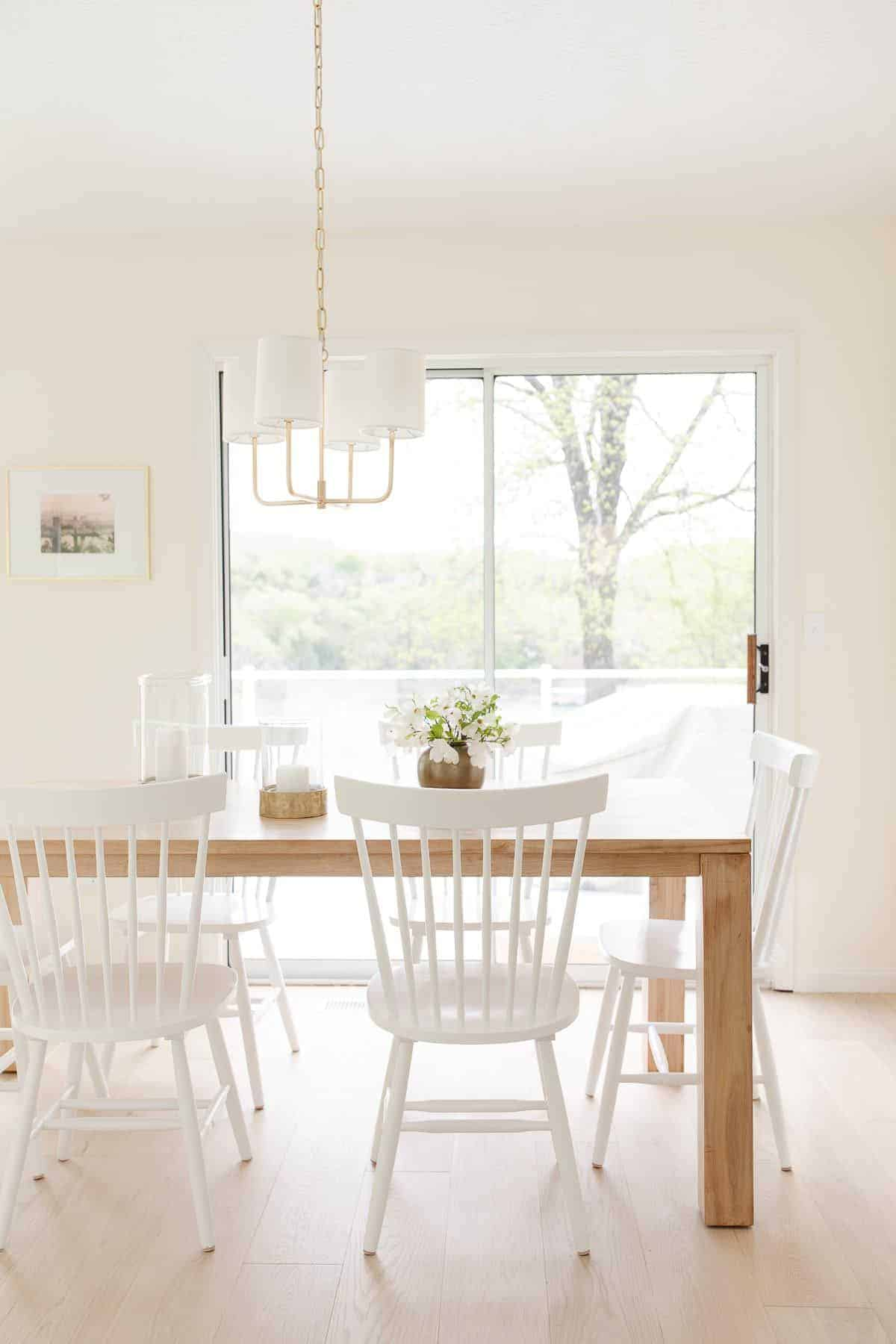 A white kitchen dining area with large white oak floors.