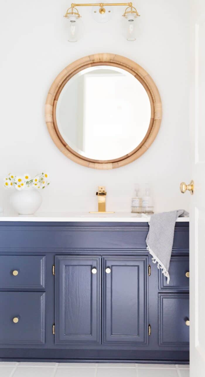 A white bathroom with a vanity painted on Benjamin Moore Hale Navy.
