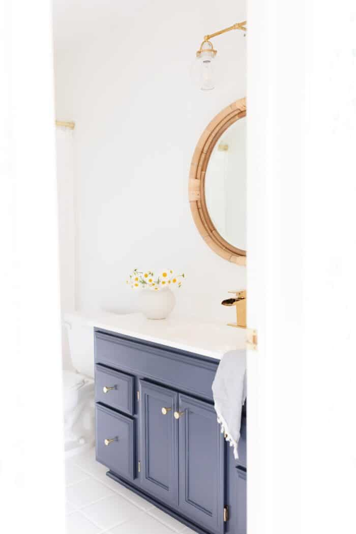 A nautical-inspired bath with white walls and a wooden vanity painted with Benjamin Moore Hale Navy paint.