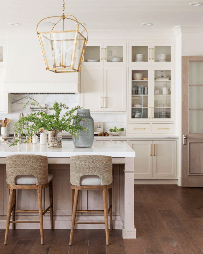 A warm white kitchen painted with Benjamin Moore Swiss coffee paint, with a golden lantern on the island.