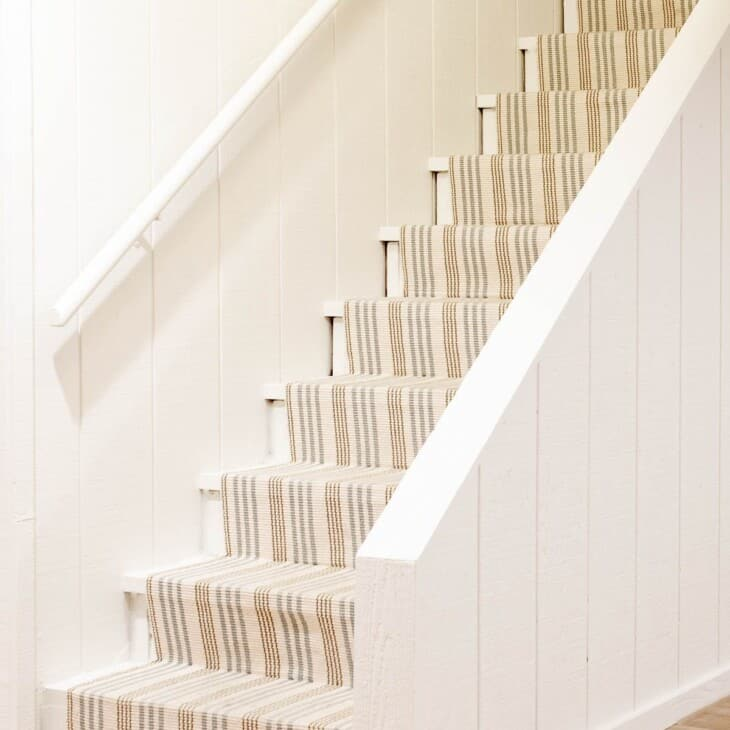 Basement stairs with a striped runner and Benjamin Moore Swiss Coffee warm cream paint color on the walls.