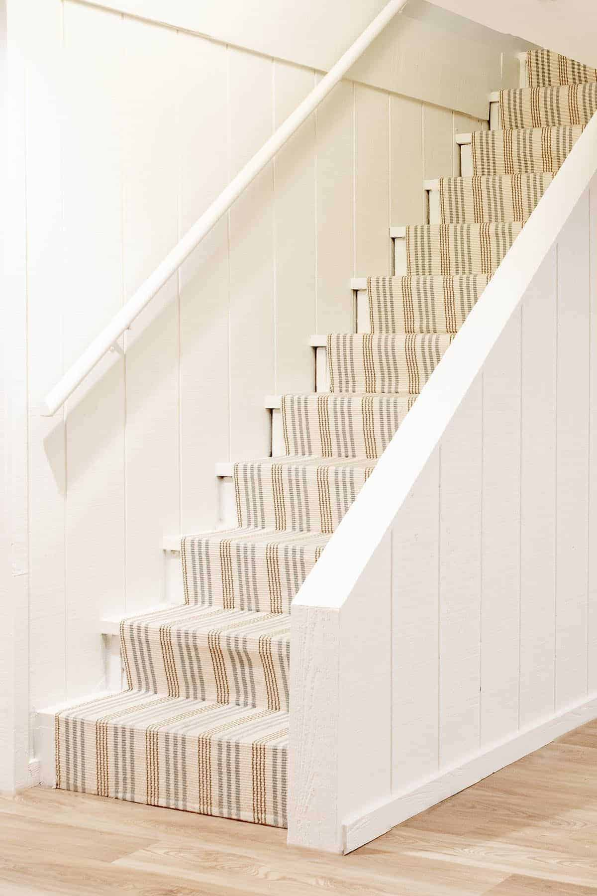 Basement stairs with a striped hallway and Benjamin Moore Swiss Coffee warm cream-colored on the walls.