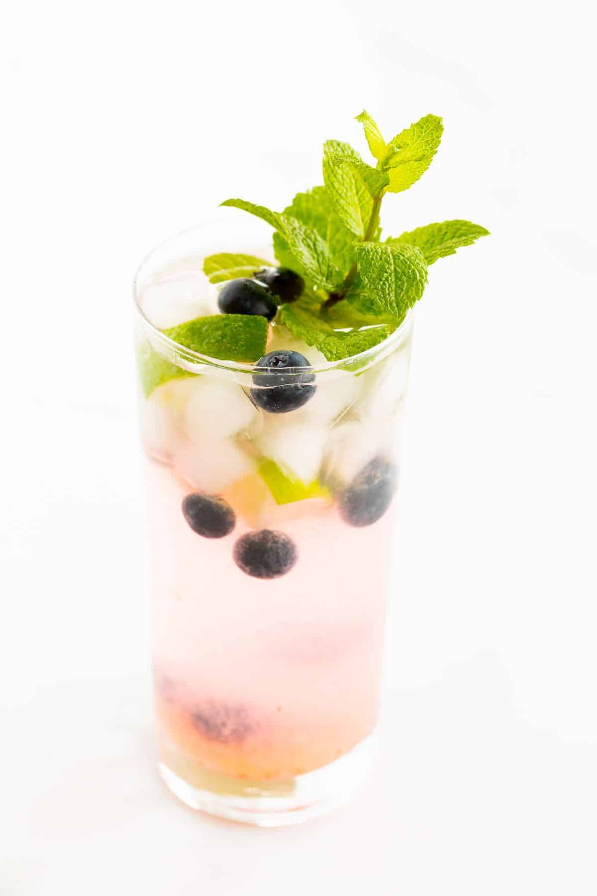 A fresh blueberry mojito recipe garnished with mint, lime and blueberries on a marble surface.