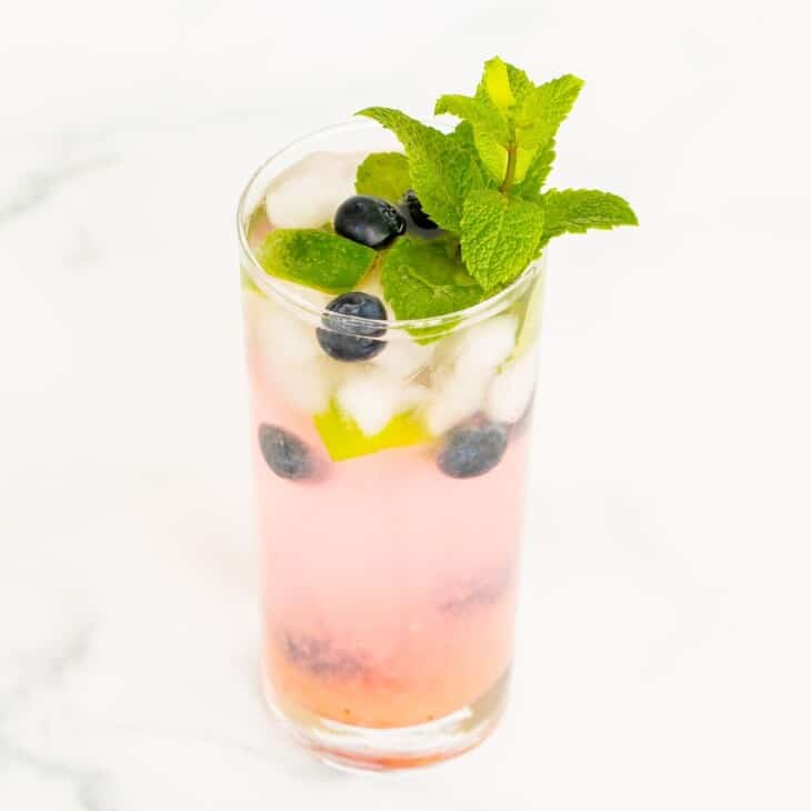 A fresh blueberry mojito garnished with mint, lime and blueberries on a marble surface.