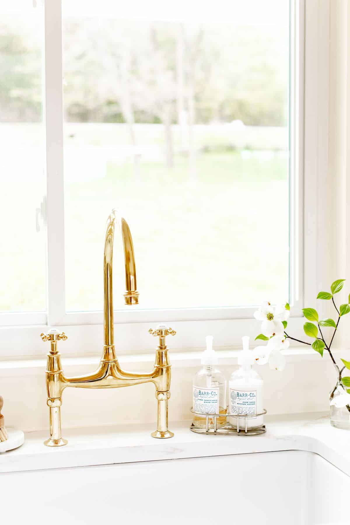 A white kitchen sink area with a brass bridge faucet, window over the sink and vase of flowers to the side.