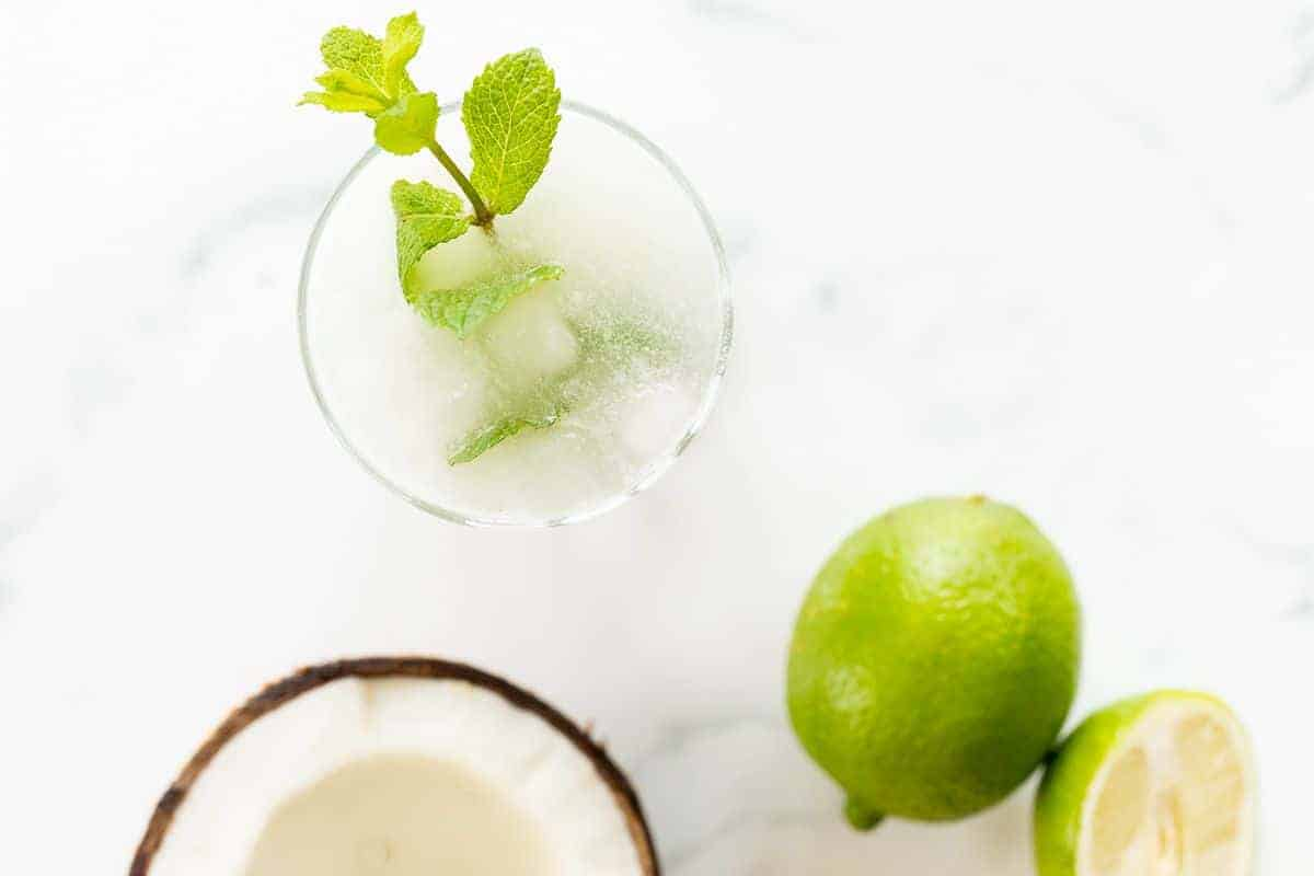On a marble surface, a coconut mojito garnished with mint, half a coconut and a full lime near the glass.