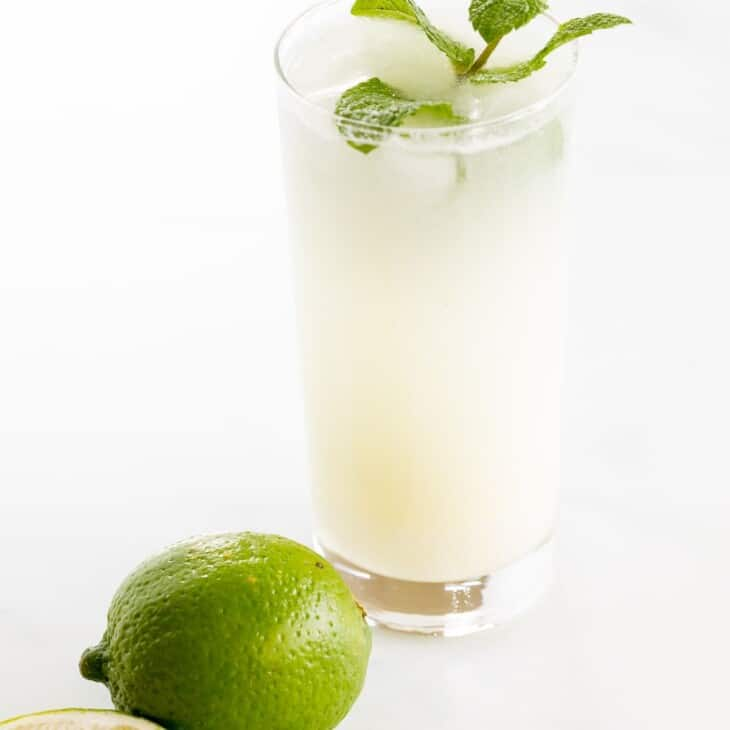 A coconut mojito garnished with mint on a marble surface.