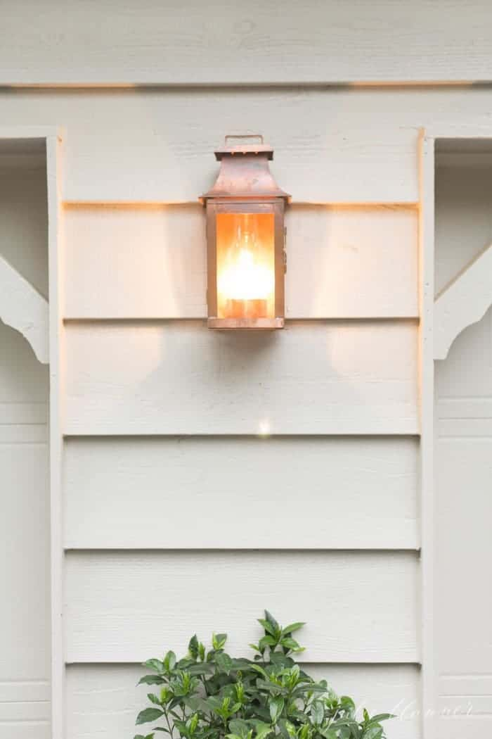 A copper wall lantern on the outside of a house.