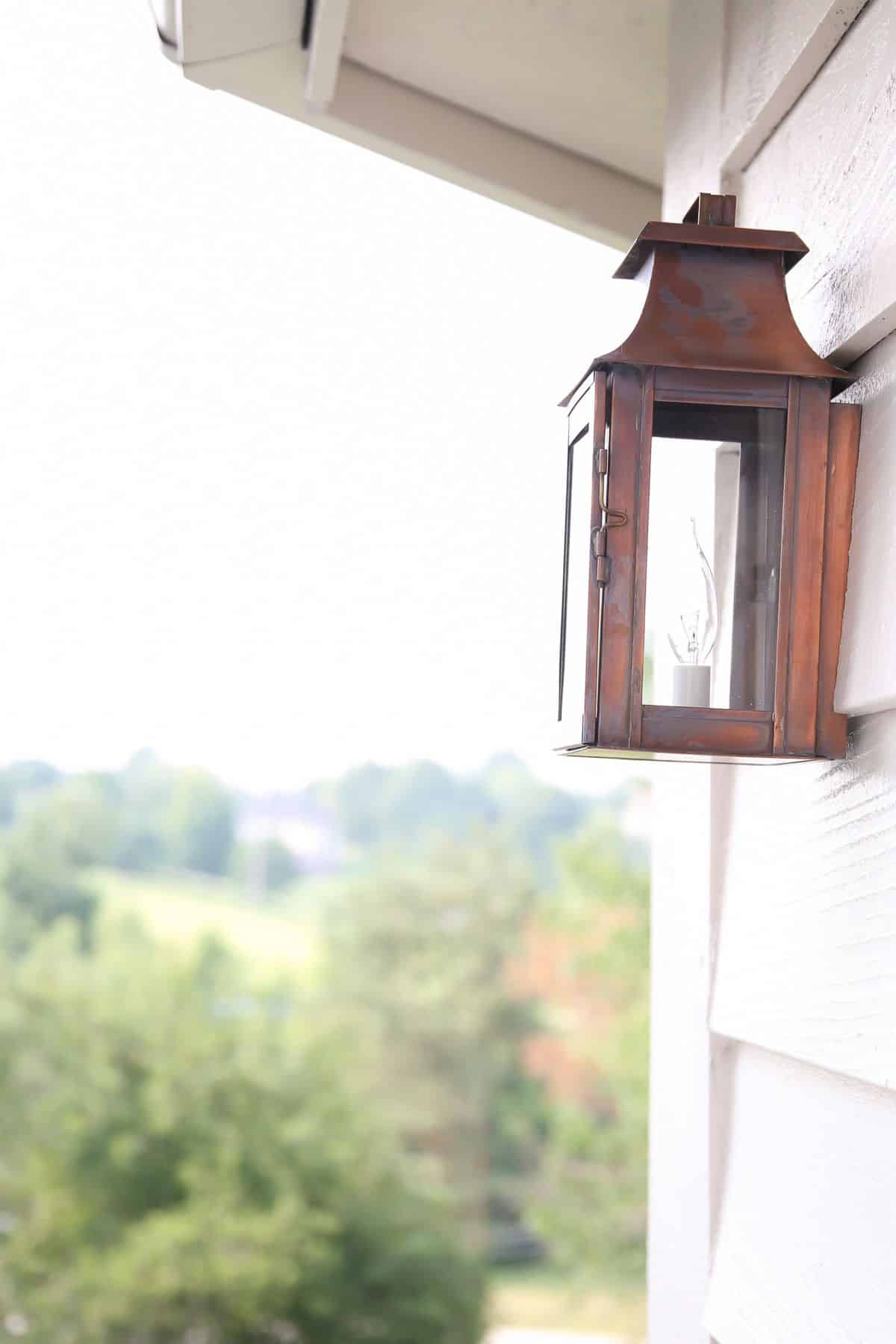 A copper lantern on the side of a house, trees in the background.