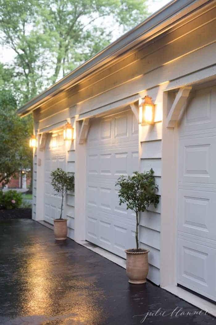 Copper outdoor wall lights on the exterior of a home between garage doors.