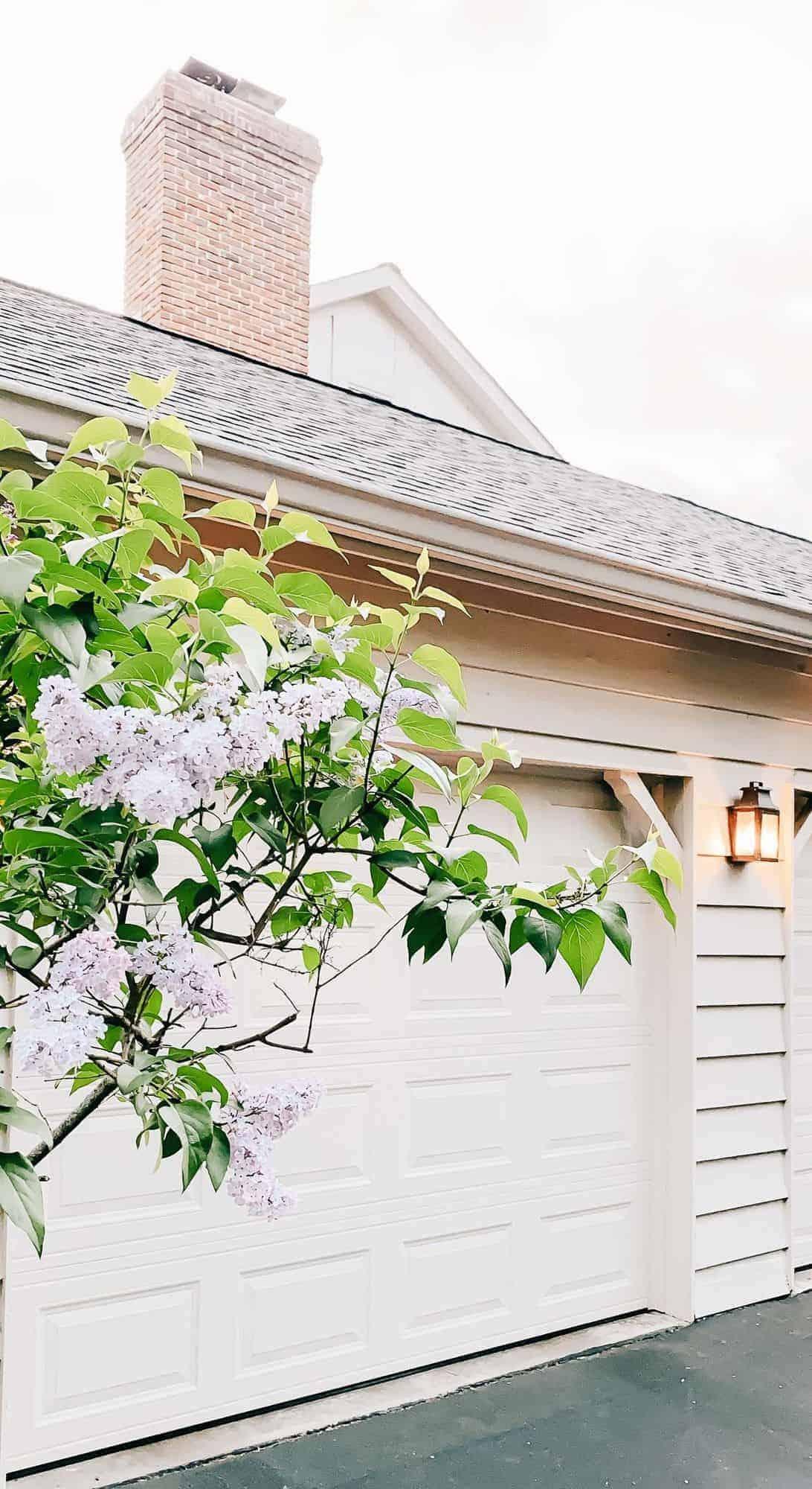 An exterior of a home with a copper lantern near a garage door.
