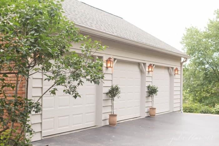 Copper outdoor lanterns on the exterior of a home between garage doors.