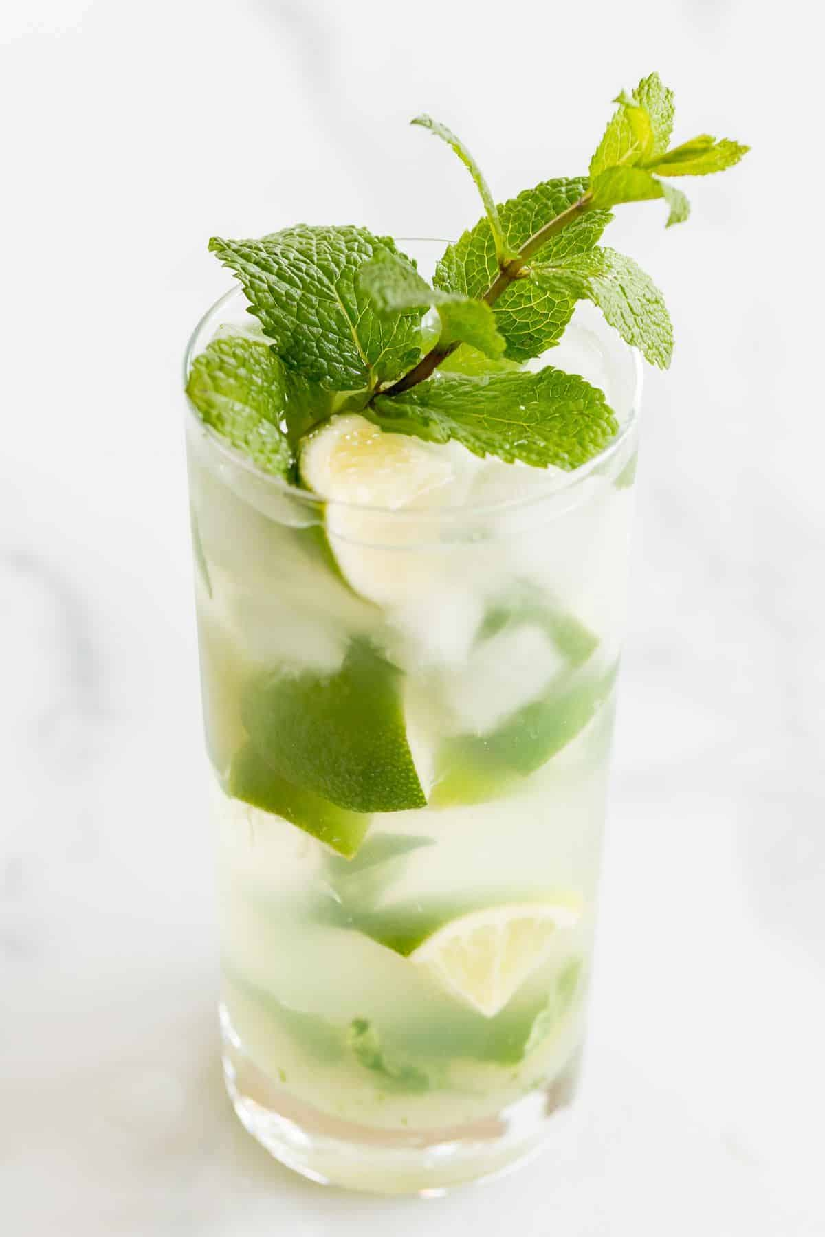 A gin mojito recipe in a clear glass, garnished with mint and lime on a marble surface.