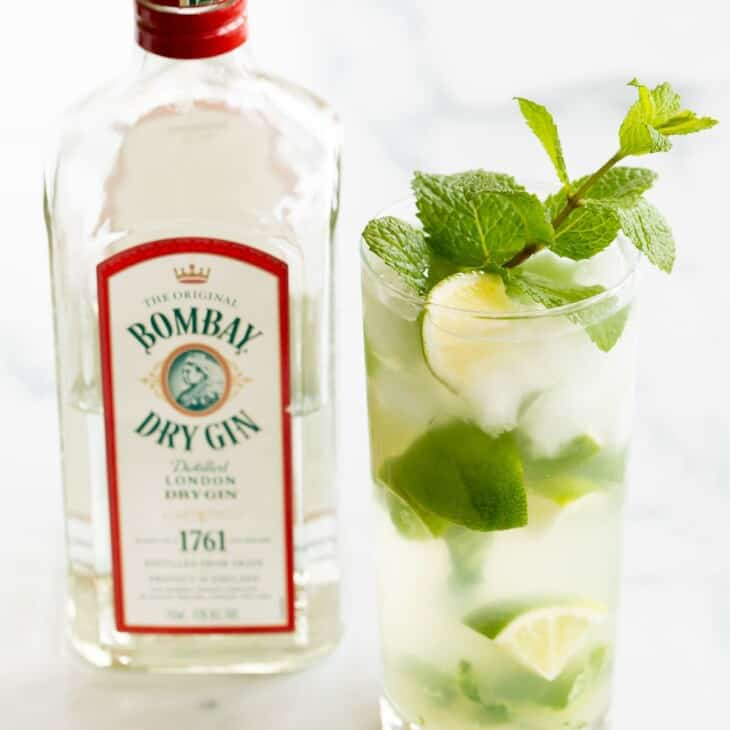 A gin mojito in a clear glass, garnished with a wedge of lime and a sprig of mint. Gin bottle in background.