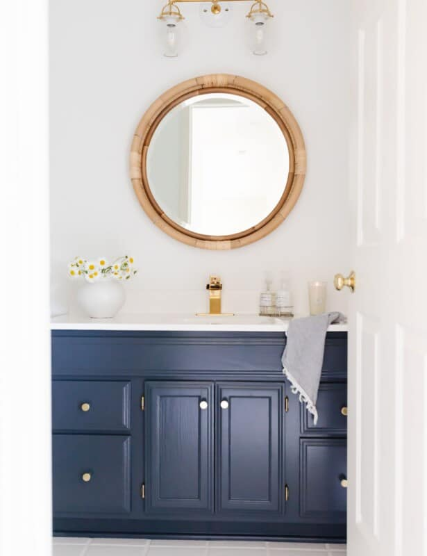 A white bathroom with a round rattan mirror and a dark blue vanity.
