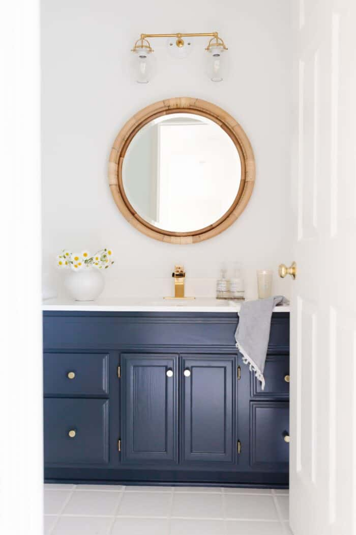 A white bathroom with a round wicker mirror and a dark blue vanity painted on the HC-154.