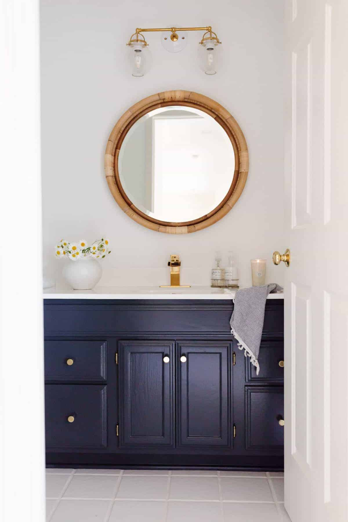 A white bathroom with a round wicker mirror and a dark blue dressing table.
