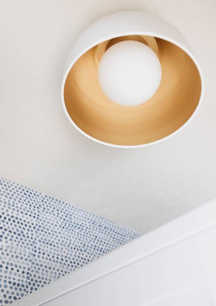 A modern gold flush mount light fixture near a blue and white polka dot wallpaper.