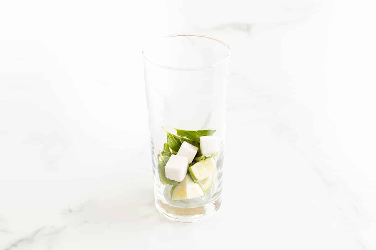 A clear glass filled with sugar cubes, mint leaves and lime wedges on a marble surface.