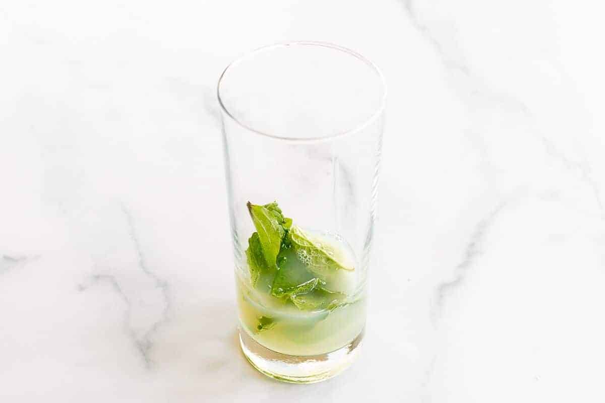 A clear glass filled with simple sugar and mint leaves.
