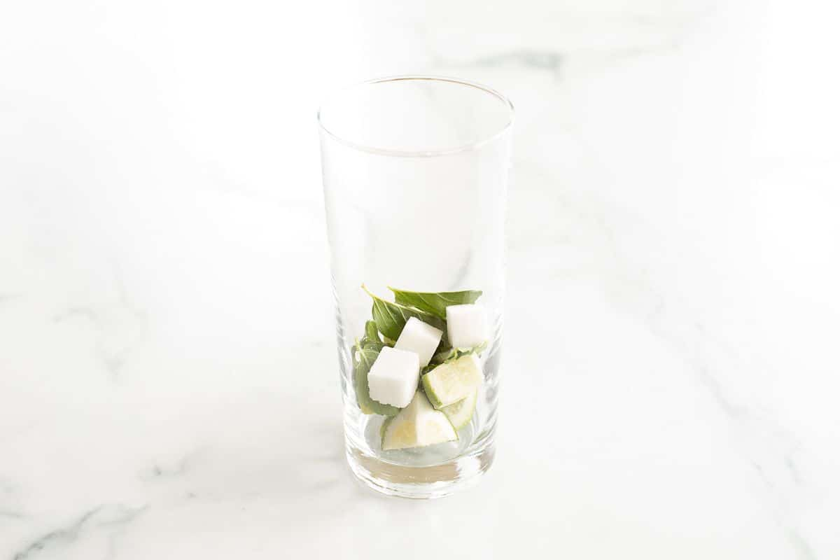 A clear glass filled with sugar cubes and mint leaves.