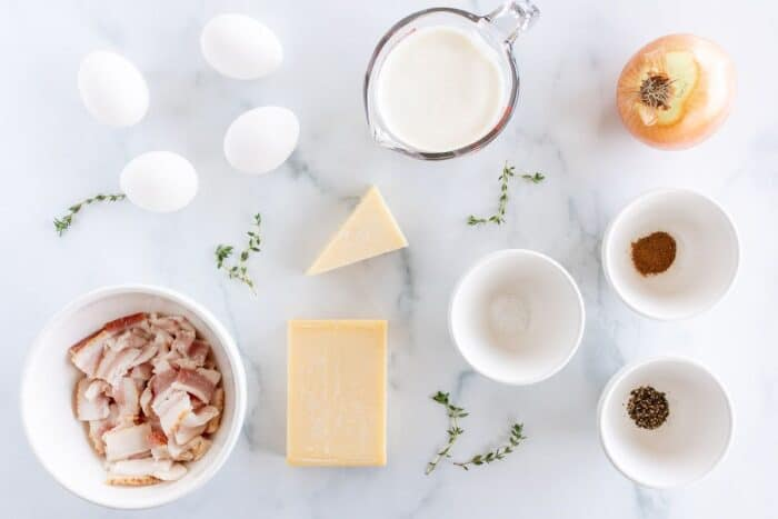 Quiche lorraine recipe ingredients laid out on a marble surface.