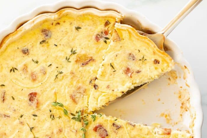 A quiche lorraine recipe in a white pan, one slice removed and another being cut away.